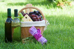 Outdoor picnic basket with wine on lawn Royalty Free Stock Photo
