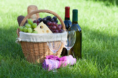 Outdoor picnic basket with wine on lawn Stock Images