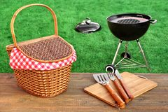 Outdoor Picnic Or BBQ Grill Party Scene At Summertime. Picnic Table With Hamper And Grill Tools Close-up, Barbecue Appliance On The Fresh Lawn In The Royalty Free Stock Images
