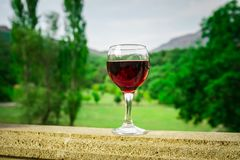 Outdoor picnic setting with wine or glass of wine on balcony with green field and mountains on background royalty free stock images