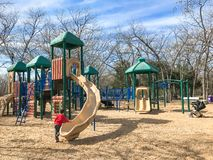 Outdoor playground with children playing wintertime in North Texas, America. Kids running at colorful playground during wintertime in Lewisville, Texas, USA stock photo