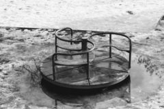 Outdoor playground, old swings, always alone in winter. Puddles of mud, snow that melts retro swing swings for poor children for free quarters stock photography
