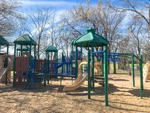 Outdoor playground surrounded by bare trees in wintertime in North Texas, America. Colorful playground at sunny day of wintertime in Lewisville, Texas, USA royalty free stock image