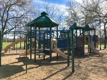 Outdoor playground surrounded by bare trees in wintertime in North Texas, America. Colorful playground at sunny day of wintertime in Lewisville, Texas, USA royalty free stock photos