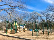 Outdoor playground surrounded by bare trees in wintertime in North Texas, America. Colorful playground at sunny day of wintertime in Lewisville, Texas, USA stock images