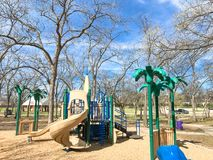 Outdoor playground surrounded by bare trees in wintertime in North Texas, America. Colorful playground at sunny day of wintertime in Lewisville, Texas, USA stock photography