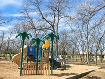 Outdoor playground surrounded by bare trees in wintertime in North Texas, America. Colorful playground at sunny day of wintertime in Lewisville, Texas, USA royalty free stock images