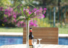 Outdoor pleasure. Vase containing flowers and bottle of wine and two wine glasses on wooden table with chair in view set in front of swimming pool Royalty Free Stock Photo