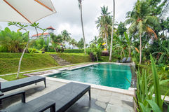 Outdoor pool area of Luxury Bali villa. Bali - Indonesia. Outdoor pool area of luxury villa in Bali with a garden and located in the edge of brink stock images