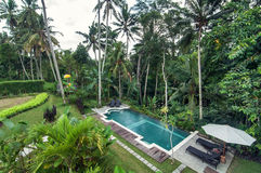 Outdoor pool area of Luxury Bali villa. Bali - Indonesia. Outdoor pool area of luxury villa in Bali with a garden and located in the edge of brink stock image