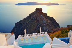 Luxury outdoor pool sea view Santorini island Greece. Outdoor pool of luxurious holiday villa perched on the top of Caldera overlooking Scaros rock-tourist Royalty Free Stock Photo