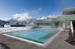 Outdoor pool which is steaming. At a cold and clear winter day and mountains in the background Stock Image