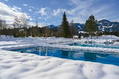 Outdoor Pools at winter time with snow around at snowy Rest Area with Deckchairs in Resort in Bavaria, Germany on winter day. Different outdoor pools of Hotel stock photography