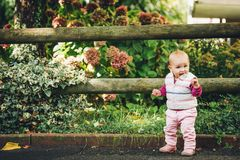Adorable baby girl playing outside. Outdoor portrait of adorable baby girl of 9-12 months old playing in the park, wearing white bodywarmer Stock Image
