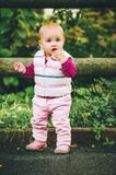 Adorable baby girl playing outside. Outdoor portrait of adorable baby girl of 9-12 months old playing in the park, wearing white bodywarmer Royalty Free Stock Image