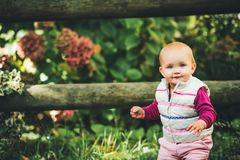 Adorable baby girl playing outside. Outdoor portrait of adorable baby girl of 9-12 months old playing in the park, wearing white bodywarmer Royalty Free Stock Photos