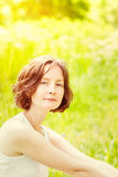 Outdoor portrait of adorable freckled young woman. Who sitting on green grass in summer park on sunny day . Orange and yellow natural toning royalty free stock photo