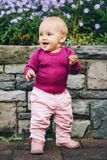 Adorable baby girl playing outside. Outdoor portrait of adorable 9-12 month old baby girl playing with purple flowers, wearing pink trousers, leather boots and Royalty Free Stock Image