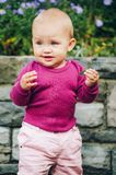 Adorable baby girl playing outside. Outdoor portrait of adorable 9-12 month old baby girl playing with purple flowers, wearing pink trousers and purple body Stock Photo