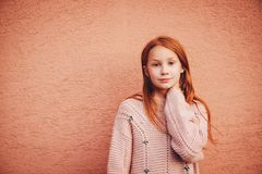 Outdoor portrait of cute preteen girl. Outdoor portrait of adorable red-haired preteen girl wearing soft pink pullover, kid model posing against beige wall Stock Image