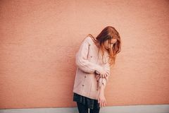 Outdoor portrait of cute preteen girl. Outdoor portrait of adorable red-haired preteen girl wearing soft pink pullover, kid model posing against beige wall Royalty Free Stock Photo