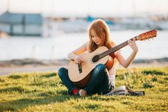 Outdoor portrait of adorable 9 year old kid girl playing guitar outdoors. Sitting on bright green lawn at warm summer sunset royalty free stock photo