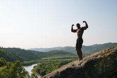 Outdoor portrait of african american bodybuilder with naked torso posing on the rock. Green mountain nature background Royalty Free Stock Photography