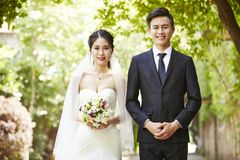 Outdoor portrait of a newly-wed asian couple royalty free stock image