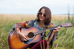 Outdoor portrait of attractive female with dark hair wearing sunglasses playing acoustic guitar demonstrating her talent having th stock image