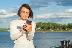 Outdoor portrait attractive happy middle aged woman female freelancer blogger traveler with phone on nature stock images