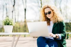 Outdoor portrait of attractive young girl with fluffy blonde hair wearing sunglasses, jeans and green jacket holding laptop comput stock images