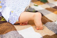 Outdoor portrait of a baby on all fours. crawling on knees child. On the grass in a summer park, set Stock Image