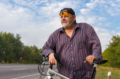 Outdoor portrait of a bearded senior man with bicycle Stock Photo