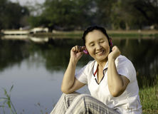 Beautiful asian woman listening music in headphones with closed Royalty Free Stock Images