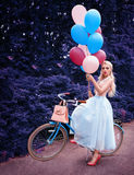 Outdoor portrait of a beautiful blonde girl holding balloons and riding a bike. In the park stock photos
