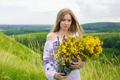 Outdoor portrait of beautiful blonde woman, attractive young girl in camomile field with flowers. Young beautiful girl in the fiel Royalty Free Stock Images