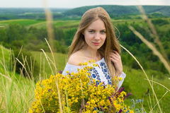 Outdoor portrait of beautiful blonde woman, attractive young girl in camomile field with flowers. Young beautiful girl in the fiel Stock Photography