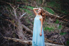 Outdoor portrait of a beautiful brunette model in blue dress in the spring forest.  Stock Photo
