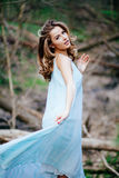 Outdoor portrait of a beautiful brunette model in blue dress in the spring forest.  Royalty Free Stock Image