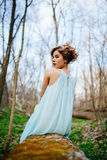 Outdoor portrait of a beautiful brunette model in blue dress in the spring forest.  Royalty Free Stock Photos