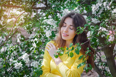 Outdoor portrait of a beautiful brunette woman among blossom trees in spring Royalty Free Stock Image