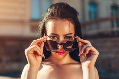 Outdoor portrait of beautiful brunette woman with make-up wearing sunglasses. Topless fashion model taking glasses off stock photos