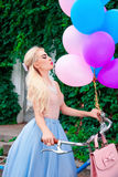 Outdoor portrait of a beautiful caucasian blonde girl holding bright balloons and a bicycle Royalty Free Stock Images