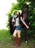 Outdoor portrait of beautiful cowgirl  with horse in green Stock Photography