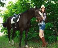 Outdoor portrait of beautiful cowgirl  with horse in green Royalty Free Stock Photography