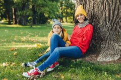Outdoor portrait of beautiful female dressed in warm cap and warm loose sweater spend weekends together with her little daughter, stock images