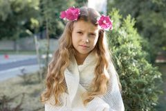 Outdoor portrait of beautiful girl child blonde with wreath of fresh pink flowers royalty free stock images