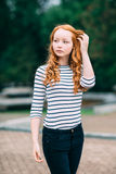 Outdoor portrait of beautiful girl with long curly red hair Stock Photo
