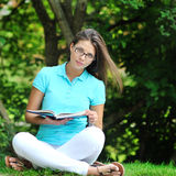 Outdoor portrait of a beautiful girl reading book in summer gree Stock Photos