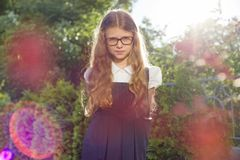 Outdoor portrait of beautiful girl 7, 8 years old with glasses school uniform royalty free stock photo
